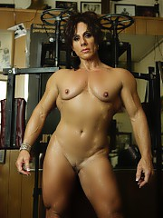 Professional female bodybuilder Annie Rivieccio works her vascular pecs and biceps barefoot in the gym, taking off her shoes and panties and posing nude to show you how ripped her muscular abs, legs and glutes are.